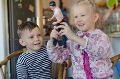 Petite fille heureuse et garçon jouant avec une poupée Photographie stock libre de droits