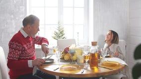 Petite fille heureuse et homme supérieur célébrant des vacances dans la cuisine banque de vidéos
