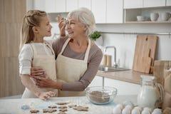 Petite-fille heureuse faisant cuire la pâtisserie avec sa grand-mère Photos stock