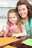 Petite fille heureuse faisant les formes de papier avec la mère à la table Photo libre de droits