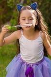 Petite fille heureuse jouant avec des bulles de savon sur une nature d'été, des accessoires de port d'un tigre d'oreilles de bleu Photographie stock
