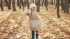 Petite fille heureuse jouant avec les feuilles d'automne en parc banque de vidéos