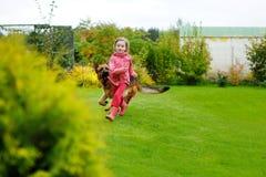Petite fille heureuse jouant avec un grand chien Photo stock