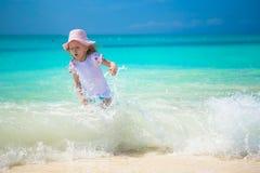 Petite fille heureuse jouant en eau peu profonde à Photo stock