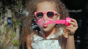 Petite fille heureuse jouant les bulles de savon extérieures et soufflantes, ayant l'amusement sur l'arrière-cour nature bel enfa clips vidéos