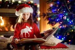 Petite fille heureuse lisant un livre d'histoire par une cheminée dans un salon foncé confortable le réveillon de Noël Photos libres de droits
