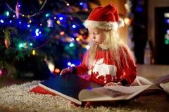 Petite fille heureuse lisant un livre d'histoire par une cheminée dans un salon foncé confortable le réveillon de Noël Photographie stock
