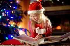 Petite fille heureuse lisant un livre d'histoire par une cheminée dans un salon foncé confortable le réveillon de Noël Images libres de droits