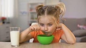 Petite fille heureuse mangeant des cornflakes avec la table à la maison se reposante de lait, nourriture saine banque de vidéos