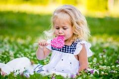 Petite fille heureuse mangeant un morceau de sucrerie sur un bâton sous forme de coeur Images libres de droits