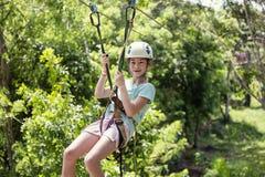 Petite fille heureuse montant une ligne de fermeture éclair dans une forêt tropicale luxuriante Photos stock