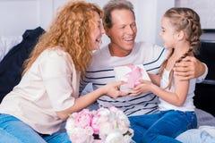 Petite fille heureuse obtenant un cadeau de ses grands-parents Photos libres de droits