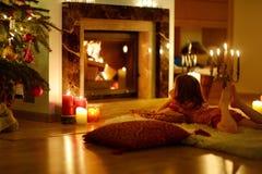 Petite fille heureuse par une cheminée sur Noël Image stock
