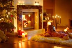 Petite fille heureuse par une cheminée sur Noël Photographie stock