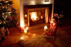 Petite fille heureuse par une cheminée sur Noël Photos libres de droits