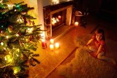 Petite fille heureuse par une cheminée sur Noël Photos stock