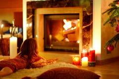 Petite fille heureuse par une cheminée sur Noël Images stock
