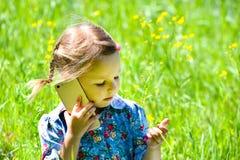 Petite fille heureuse parlant au téléphone sur la pelouse verte photos libres de droits