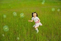 Petite fille heureuse parmi des bulles de savon Images stock
