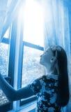 Petite fille heureuse regardant par la fenêtre Photo libre de droits