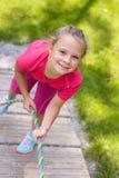 Petite fille heureuse s'élevant sur le terrain de jeu extérieur image stock