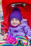 Petite fille heureuse s'asseyant dans la poussette tenant une tasse avec le casse-croûte Photographie stock