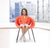 Petite fille heureuse s'asseyant sur la chaise de concepteur Photographie stock libre de droits