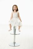Petite fille heureuse s'asseyant sur la présidence Images stock