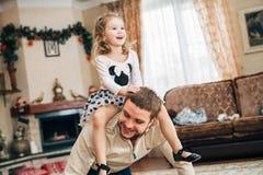 Petite fille heureuse s'asseyant sur le cou du ` s de papa Photos libres de droits