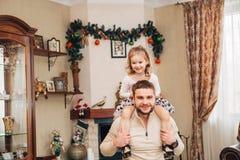 Petite fille heureuse s'asseyant sur le cou du ` s de papa Photographie stock