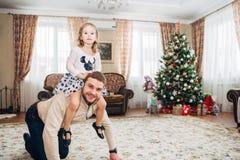 Petite fille heureuse s'asseyant sur le cou du ` s de papa Photo libre de droits