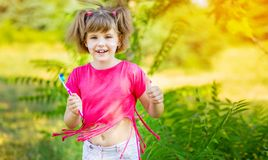 Petite fille heureuse se brossant les dents avec des pouces  Hygi?ne dentaire image libre de droits