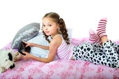 Petite fille heureuse se trouvant sur le lit avec la tablette image stock