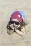 Petite fille heureuse se trouvant sur le sable sur la plage image stock