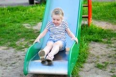 Petite fille heureuse sur la glissière en parc d'été Photo stock