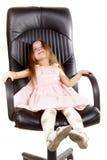 Petite fille heureuse sur la présidence de bureau photo stock