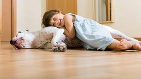 Petite fille heureuse sur le plancher avec le chien Images libres de droits
