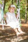 Petite fille heureuse sur une oscillation Images stock