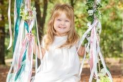 Petite fille heureuse sur une oscillation Image stock