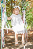Petite fille heureuse sur une oscillation Photo stock