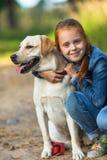 Petite fille heureuse sur une promenade avec le chien Images stock