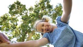 Petite fille heureuse tournant autour avec la mère en parc banque de vidéos