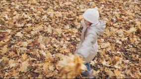 Petite fille heureuse tournant avec le petit bouquet des feuilles d'automne en parc banque de vidéos