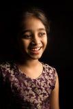 Petite fille indienne dans la robe traditionnelle, d'isolement sur le fond noir image stock
