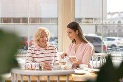 Petite-fille inspirée prenant le déjeuner avec sa mamie Image stock