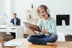 Petite fille intuitive jouant avec son comprimé images stock