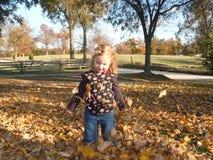 Petite fille jetant Autumn Leaves en l'air Photos stock