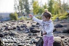 Petite fille jetant les pierres image libre de droits