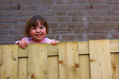 Petite fille jetant un coup d'oeil au-dessus de la frontière de sécurité Images libres de droits