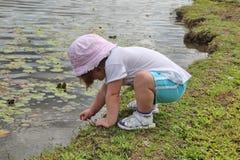 Petite fille jouant à côté du lac Photos stock